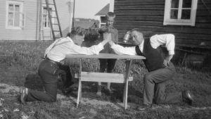 Två män bryter arm. Fotografiet är taget år 1929 i Pyttis, Kvarnby.