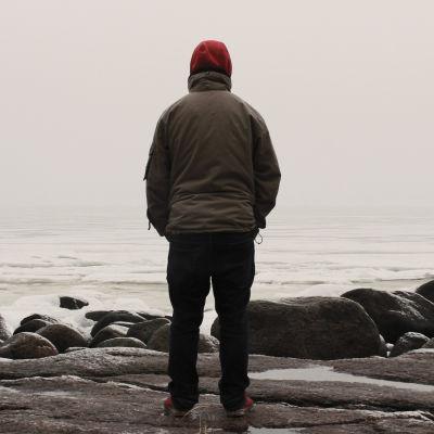 En person står ensam och tittar ut över havet.