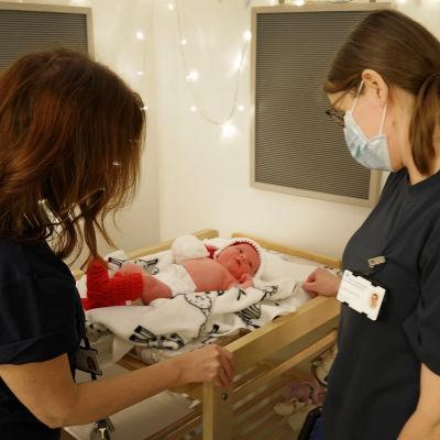 Barnmorskor sköter om en nyfödd.