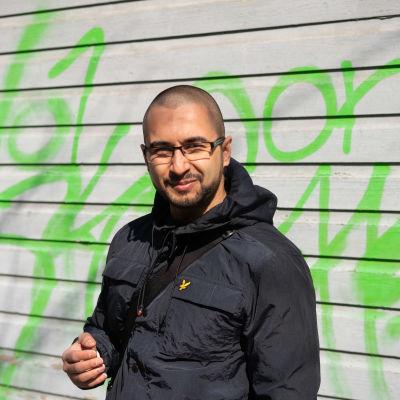 En man står framför en trävägg, där det finns streck sprayade med grön färg.