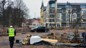 Man med skyddsväst går på en byggarbetsplats.