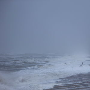 Stormvågor slår mot strand.
