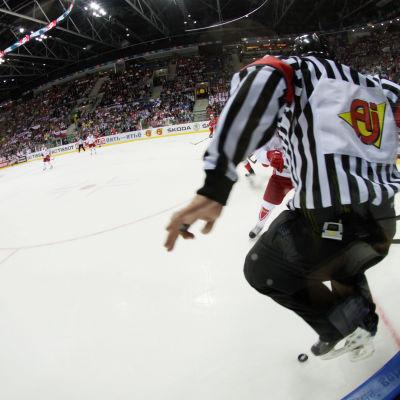 En ishockeydomare hoppar för att akta sig för pucken.