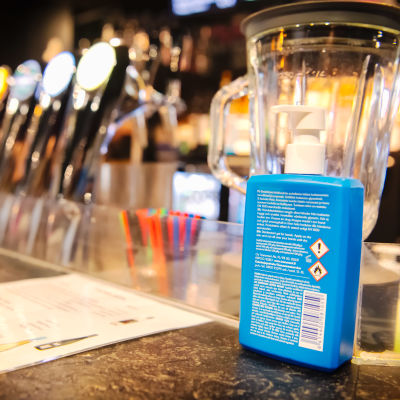En blå flaska med handdesinfektionsmedel på en bardisk