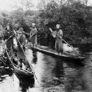En svartvit bild på allvarliga män i kanoter.
