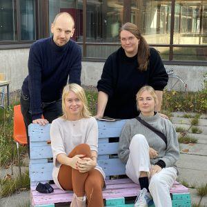 En man och tre kvinnor sitter på en bänk utomhus.