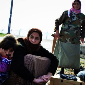 Yazidiska kvinnor sitter på huk på marken i ett flyktingläger
