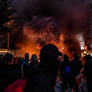 G20-demonstranter vid området Schanzenviertel i Hamburg står vid brinnande barrikader med ett stort rökmoln som stiger upp i luften.