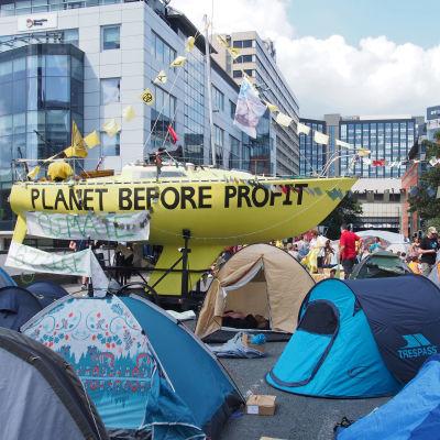 """En segelbåt på en gata, omringad av tält. På den gulmålade båten står det """"Planet before profit""""."""