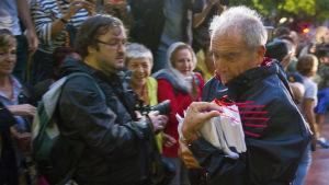 En man bär in röstsedlar till en vallokal i Barcelona.