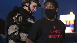 """En polis sätter handklovar på en afroamerikansk kvinna som har en svart t-skjorta med texten """"Jag kan inte andas""""."""