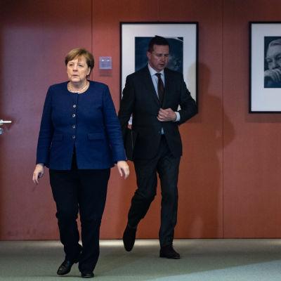 Angela Merkel ja Steffen Seibert kävelevät lehdistötilaisuuteen Saksassa maaliskuussa.