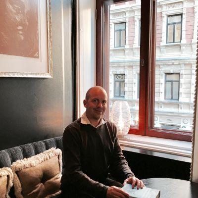 Samu Nyström sitter vid ett fönster på Hotell Kämp.
