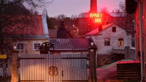 Porten till Billnäs bruk där en röd, stor digital klocka finns.