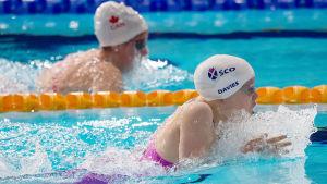 Två simmare sida vid sida under tävling.