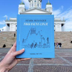 Blå bokpärm och Helsingfors domkyrka i bakgrunden.
