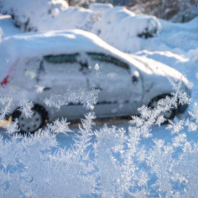 En snötäckt personbil fotograferad genom ett fönster med rimfrost.