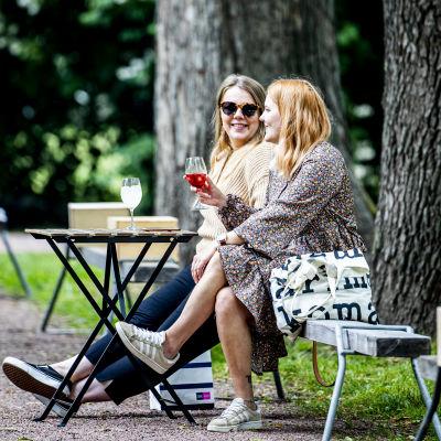Två kvinnor sitter på en uteservering.
