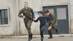 Cassie håller sin lillebror Sam i handen och springer tillsammans med Ben undan de onda.