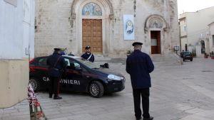 Poliser vid en polisbil utanför en kyrka i Grumo Appula.