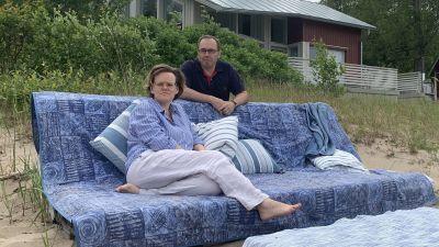 Ett par sitter i en soffa på en sandstrand med en sommarstuga i bakgrunden.