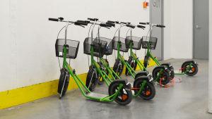 flera gröna sparkcyklar på rad mot en vit vägg.