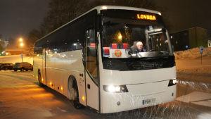 En vit buss står på en parkeringsplats. Inne i den annars tomma bussen sitter en äldre man som är chaufför. Uppe på bussen står Loviisa.