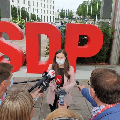 Sanna Marin intervjuas, flera personer står framför henne och räcker fram mikrofoner. I bakgrunden står det SDP med stora bokstäver.