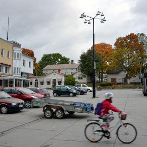 Rådhustorget i Ekenäs. Till vänster står bilar parkerade och till höger cyklar ett barn förbi.
