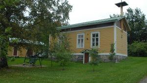 Keltainen puutalo ja pihapiiri, jossa keinu.
