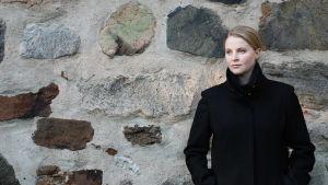 Mia Anderssén-Löf står framför en murad stenvägg.