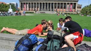 Fyra tågluffare ligger på gräsmattan i Lustgarten park i Berlin.