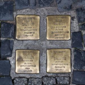 Minnesplattor ingjutna i gatan med namnen på judar som dödades av nazisterna.