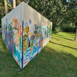 En triangelformad vägg eller ett plank som placerats ute på en gräsmatta. Det är gatukonst, graffiti målat på väggen.