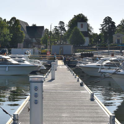En brygga där båtar ligger förtöjda. I bakgrunden syns en kyrka.