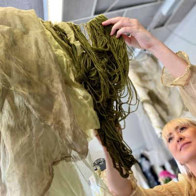 Tekstiili- ja vaatesuunnittelija Krista Virtanen ripustaa narulle punasipulin kuoriuutteella värjättyjä vihreitä lankoja.