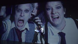 Oskar Pöysti, Jessica Kuningas och Maria Ahlroth på stor skärm, Jessica Raita och Martin Bahne framme på scenen.
