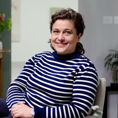 Silvia Modig småler mot kameran från en fåtölj. Hon har en blå-vit randig tröja på sig och bakgrunden syns blomkrukor.