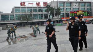 Poliser och städare utanför järnvägsstationen i staden Guangzhou i Kina där 6 personer dödades i en knivattack den 6 maj 2014.
