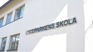 Ljus husvägg med namnet Lyceiparkens skola på