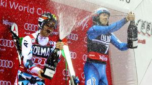 Henrik Kristoffersen och Marcel Hirscher firar på pripallen i Madonna di Campiglio.
