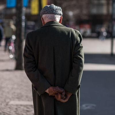 En eldre man med ryggen mot kameran. Han är iklädd paleteau, hatt och har händerna bakom ryggen.