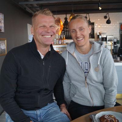 Jonte Wingren i en svart tröja och Sara Åström i en grå tröja. De sitter på ett café, i bakgrunden syns caféets kassa.