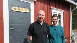 Två män ler utanför en röd byggnad.
