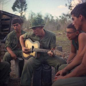 Amerikkalaissotilas soittaa kitaraa tovereilleen Vietnamin sodassa