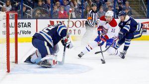 Blåklädd NHL-målvakt på knä för att stoppa puck.