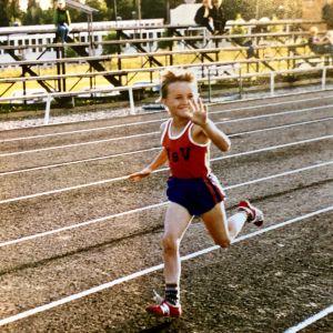Kymmenenvuotias poika juoksee urheilukentällä vasen käsi kohotettuna.