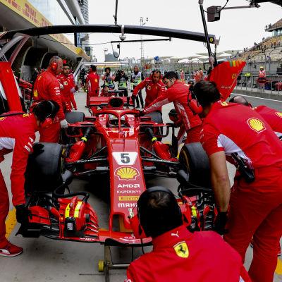 Mekaniker kring Ferraris formel 1-bil.
