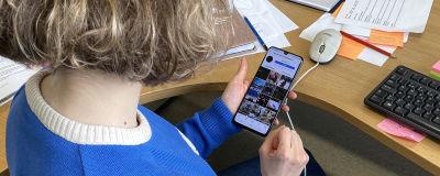Kuvassa nainen katsoo kännykältä Instagarmin kuvia
