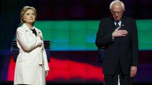 Hillary Clinton och Bernie Sanders lyssnar till nationalsången inför en valdebatt  i New York i april 2016